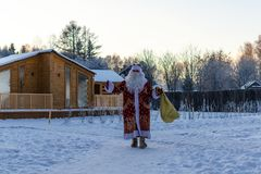 Xmas, cold, December. Santa Claus going with a bag of gifts in the winter on snow-covered field. N stock photography