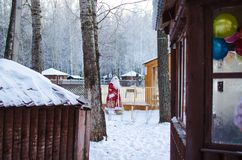Xmas, cold, December. Santa Claus going with a bag of gifts in the winter on snow-covered field stock images