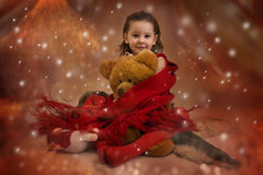 Xmas comes. Little girl at home on the Xmas tree background Royalty Free Stock Photography