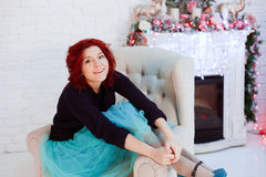 Xmas is coming. Red haired girl sitting near the fireplace Royalty Free Stock Image