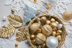 Xmas composition. Golden nuts, shell, beads and white ball lying in the basket on the christmas backdrop Stock Photos
