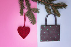 Xmas composition. Shopping bag hanging on the christmas tree twigs as decoration. Colourful background. Shop, sale and Royalty Free Stock Images