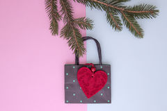 Xmas composition. Shopping bag hanging on the christmas tree twigs as decoration. Shop, sale and gifts concept. Top view Stock Images