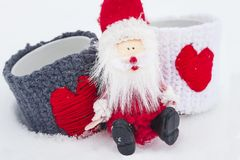 Xmas concept. Santa Claus sits on the snow with two love mugs. Christmas and New Year come. Xmas concept. Santa Claus sits on the snow with two love mugs Stock Photos