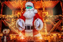 Xmas cool party. DJ Santa Claus in luminous glasses and headphones holds a party near his house decorated with lights. Christmas songs and music royalty free stock photography
