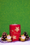 Xmas decoration. Red candle betweem two golden santa claus figures Royalty Free Stock Images
