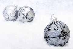 Xmas decoration. On the snow (focus on the first Bauble Royalty Free Stock Photography