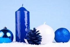 Xmas decoration - blue. Xmas decoration - candles, xmas balls and oak ball on snow Royalty Free Stock Photo
