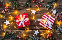 Christmas presents with white wooden stars and lights. Xmas decoration with christmas presents, white wooden stars, lights, fir twigs and red berries on wooden Stock Image