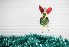Christmas photography image of xmas decoration hanging up old wood fairy with green tinsel and white wood background Stock Photos