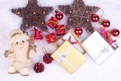 Xmas decoration on snow. Ceramic snowman, gifts, xmas balls, stars on snow Stock Photos