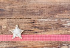 Christmas greeting card decoration with white star on red ribbon border and rustic wood background Stock Photos