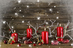 Xmas decoration on wooden rustic background: four red burning ad stock photography
