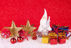 Xmas decoration - xmas card. Santa clause toy in snow on red background Stock Photography