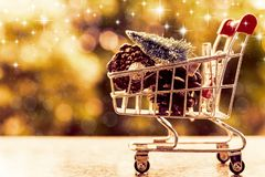 Xmas decorative items in mini shopping cart or trolley against b stock photo