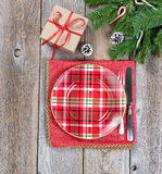 Xmas dinner setting with evergreen branches and gift box on rust Stock Image