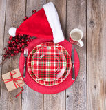 Xmas dinner setting with gift box and Santa cap on rustic wooden Stock Image