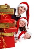 Xmas Family. Isolated studio shot of happy young family of three wearing Santa�s hats with a lot of Christmas presents Stock Images