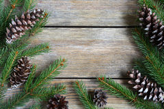 Xmas frame with green pine branch with cones on boards Royalty Free Stock Photo