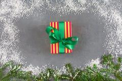Xmas-gåvaask i randigt papper, granfilialer, snöram nytt år för begrepp Royaltyfria Bilder