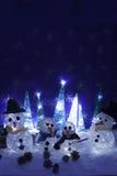 Xmas-garneringhantverk snöar scenary upplyst snögubbear och tre Arkivfoto