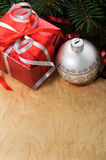 Xmas gift box and ornaments on old paper backgroun Stock Photos