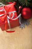 Xmas gift box and ornaments on old paper backgroun Royalty Free Stock Photo