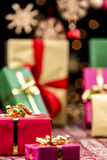 Xmas Gifts, Glitters and Stars. Twinkles, blurred stars and the hazy shapes of plain gifts in magenta, green and gold. Focus on the small red present with golden Royalty Free Stock Images