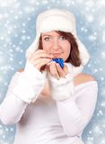 Xmas girl opening a gift with snowflakes. Cute xmas girl opening a present - on a blue background snowflakes Royalty Free Stock Image