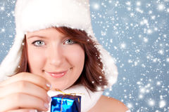 Xmas girl opening a gift while snowing. Cute xmas girl opening a blue gift - snowing around Royalty Free Stock Image
