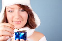 Xmas girl opening a present. Cute girl in white opening a present - focus on the present Royalty Free Stock Photo