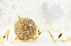 Xmas golden ball with rooster. Christmas golden ball with golden ribbon on light snowflakes background with soften silver rooster Royalty Free Stock Photos