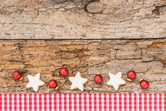 Xmas greeting card. Xmas card decorated with star cookies and christmas balls on a rustic wooden background Royalty Free Stock Image