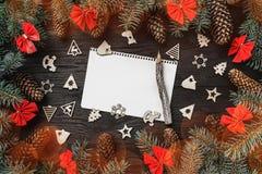 Xmas-hälsningkort med effekt för ljus kula claus bokstav santa Gran förgrena sig med kottar och röda bunkar, på svart wood bakgru arkivfoto