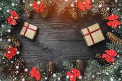 Xmas-hälsningkort med ljus och snöeffekt Gran förgrena sig med kottar och röda bunkar, på svart wood bakgrund Jul royaltyfria bilder