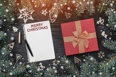 Xmas-hälsningkort med ljus och snöeffekt på svart bakgrund Röd gåva och träleksaker Granträd omkring bokstav santa royaltyfri fotografi