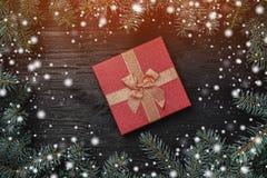 Xmas-hälsningkort med ljus och snöeffekt på svart träbakgrund Den röda gåvan i mitt av ramen av gran förgrena sig överkant royaltyfri fotografi