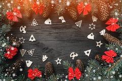 Xmas-hälsningkort med ljus och snöeffekt Utrymme för text Gran förgrena sig med kottar och röda bunkar, på svart wood bakgrund fotografering för bildbyråer