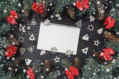 Xmas-hälsningkort med snöeffekt din avståndstext Gran förgrena sig med kottar och röda bunkar, på svart wood bakgrund royaltyfri foto