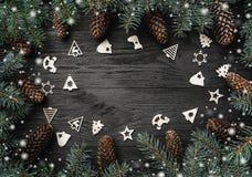 Xmas-hälsningkort med snöeffekt Smsa utrymme, introramen av granfilialer och kottar julgarneringen toys den trätreen Top beskådar royaltyfri fotografi