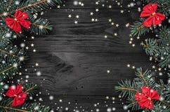 Xmas-hälsningkort, på svart träbakgrund Med granfilialer och röda bunkar Utrymme för text Top beskådar Snöeffekt arkivbilder