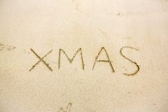 Xmas hand writing on sand beach. christmas sign on natural brown background.celebrate christmas festival with the natural is conce. Pt. image for background royalty free stock photography
