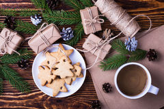 Xmas holiday background with homemade christmas cookies, cup of. Coffee,  blank card for holiday message, spruce twigs and gift boxes, top view Royalty Free Stock Photography