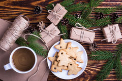 Xmas holiday background with homemade christmas cookies, cup of. Coffee,  blank card for holiday message, spruce twigs and gift boxes, top view Stock Photo