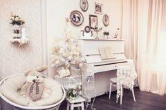 Xmas-inredesignen inkluderar den vit dekorerade julgranen med handen - gjorda prydnader, gåvaaskar under den och det vita pianot  Royaltyfri Bild
