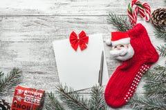 Xmas kartka z pozdrowieniami Biały drewniany tło, Bożenarodzeniowa pończocha z Santa i ja z barwionymi cukierkami inside, Obrazy Royalty Free