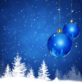 Xmas Land. Winter blue snow background with xmas balls and forest Stock Photo