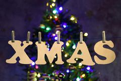 Christmas background with name XMAS. Downward composition. Xmas. Letters of plywood hang on the clothesline stock photo