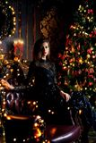 Xmas in luxurious apartments. Magical Christmas night. Beautiful woman in evening dress celebrates Christmas in luxurious apartments decorated christmas lights stock photos