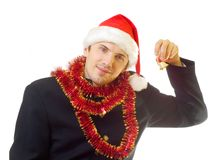 Xmas man 9. A man dressed in suit, xmas hat and tinsel ringing bell; over white background royalty free stock photos
